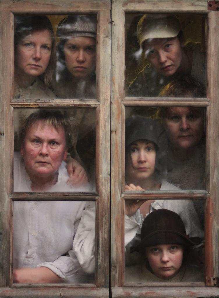 Kilpailun voittokuva, ikkuna josta näkyy useita kasvoja,.